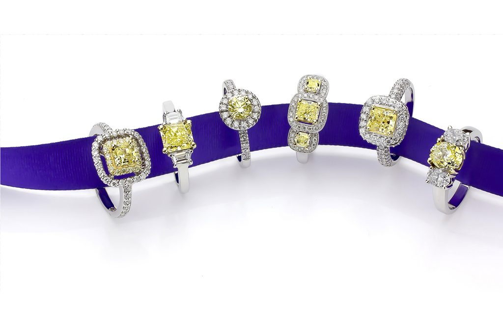 Purple ribbon through yellow diamond rings on white by Canaan Albright